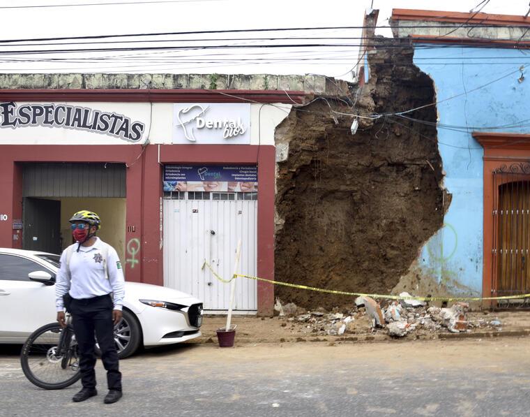 Un policía permanece de pie el martes 23 de junio de 2020 frente a una construcción que sufrió daños tras un terremoto en Oaxaca, México.