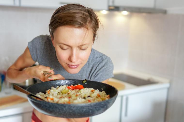 Mujer saboreando un platillo con arroz.