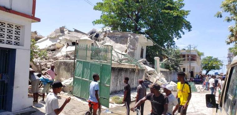 Un grupo de personas observaba los escombros de la residencia de un obispo católico que fue afectada por el sismo Les Cayes, Haití, el 14 de agosto de 2021.