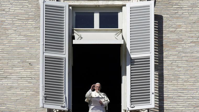 El papa Francisco bendice a los fieles desde una ventana del palacio apostólico que da hacia la Plaza de San Pedro, el domingo 9 de noviembre de 2014