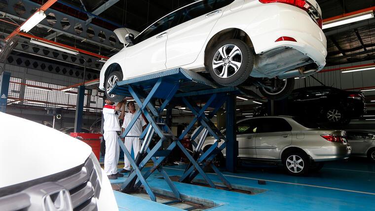 Mecánicos trabajan en auto Honda