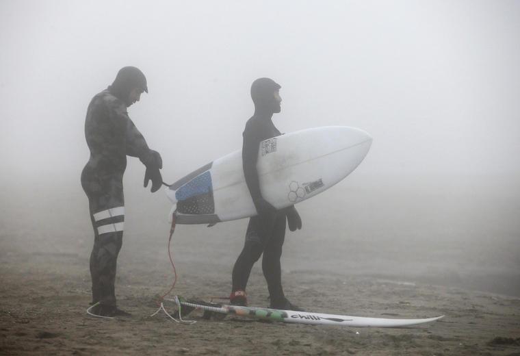surfistas en la playa en invierno