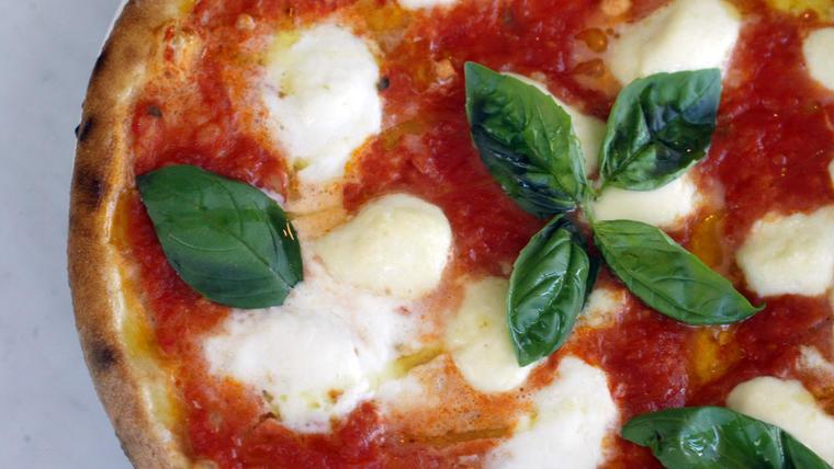 Pizza margarita con hojas de albahaca