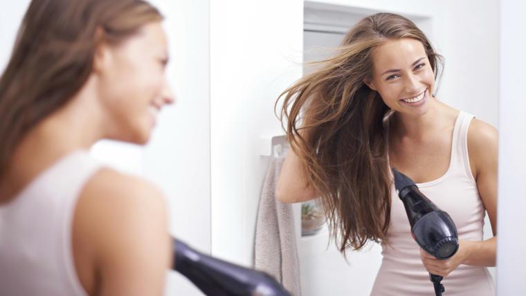 Mujer secándose el pelo frente al espejo