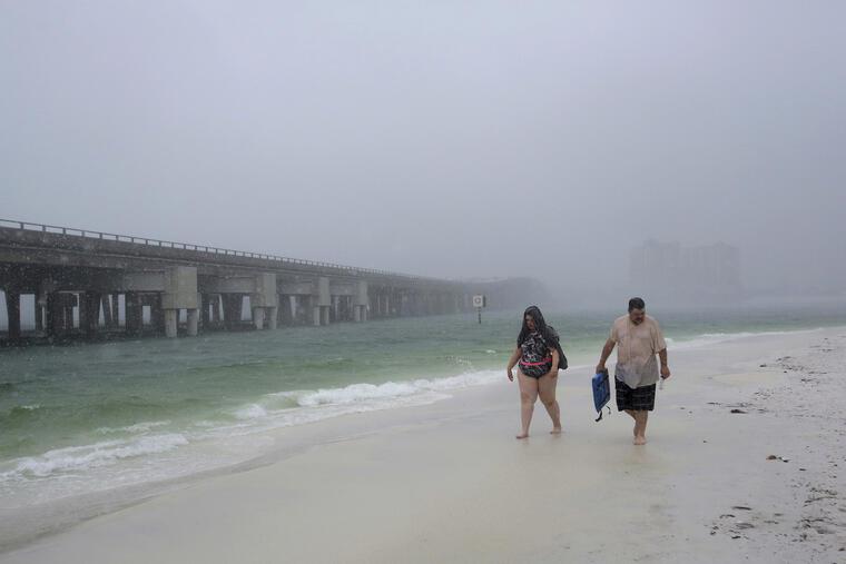 Una pareja camina entre la lluvia desatada por la tormenta subtropical hoy en Destin, Forida.