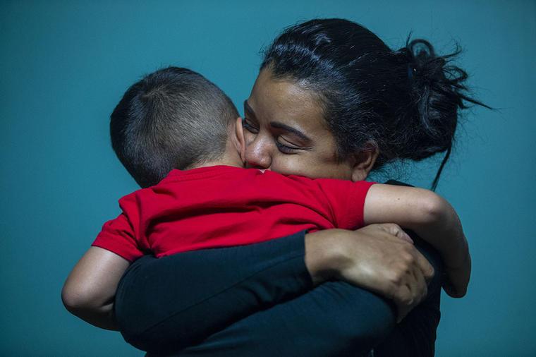 Una madre adoptiva abraza a un pequeño niño que se encuentra separado de sus padres biológicos.