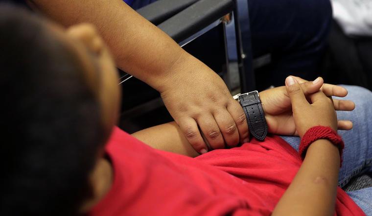 Una madre inmigrante sujeta la mano de su pequeño hijo tras haber sido reunidos.