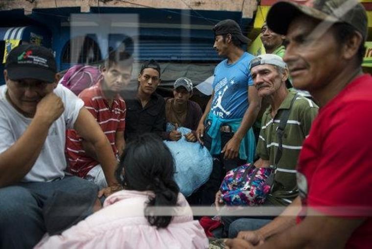 Migrantes hondureños viajan a bordo de la parte trasera de una camioneta tipo pick up en Guatemala