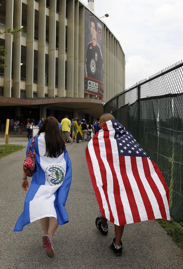 Asistentes a un partido de Fútbol llevan la bandera de El Salvador y Estados Unidos