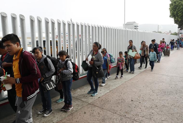 Familias cruzando la frontera de México con Estados Unidos en Tijuana