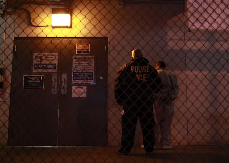 Oficial de inmigración escolta a un sujeto afuera de un centro de detención en Los Ángeles, California