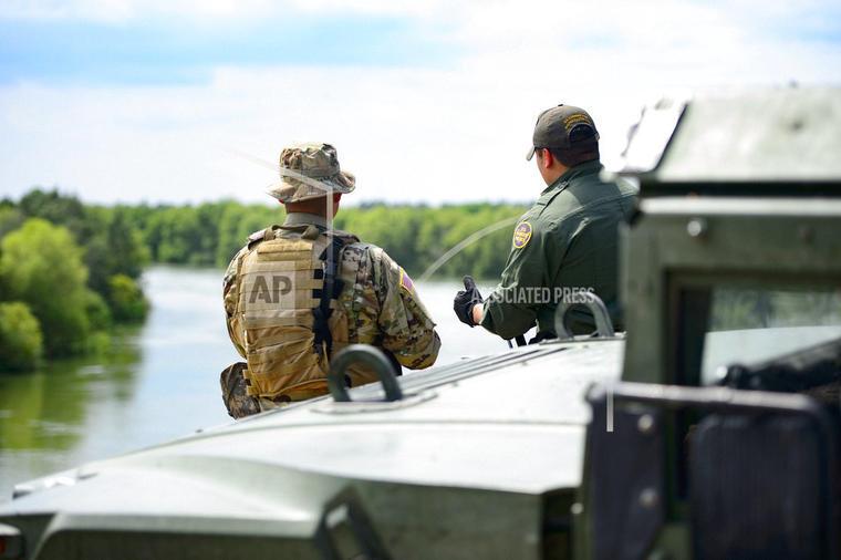 Un elemento de la Guardia Civil de Texas y un agente de la Patrulla Fronteriza discuten frente al Río Grande en la frontera con México