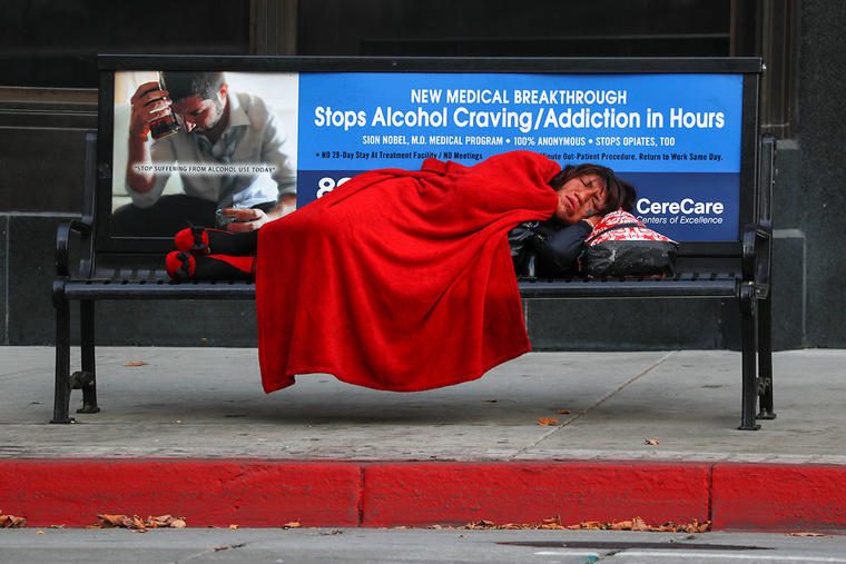 Una persona sin hogar duerme en el asiento de una parada de bus en Los Ángeles, California.
