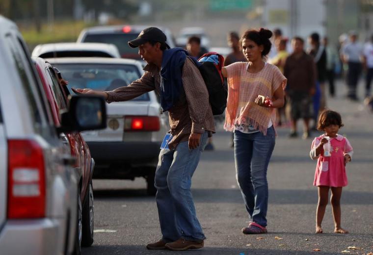 Migrantes centroamericanos piden dinero este domingo a los autos que pasan en Córdoba, estado de Veracruz, México. Ayer, la mayor parte de la caravana llegó a esta ciudad colonial.
