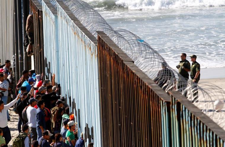 Migrantes miran este miércoles a través de la cerca fronteriza entre México y Estados Unidos.