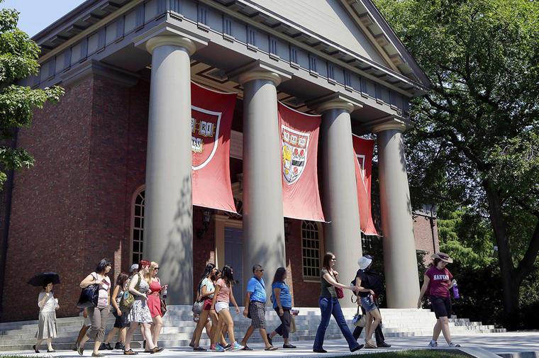 Varias personas caminan por un campus de la Universidad de Harvard, en Cambridge, Massachussetts.