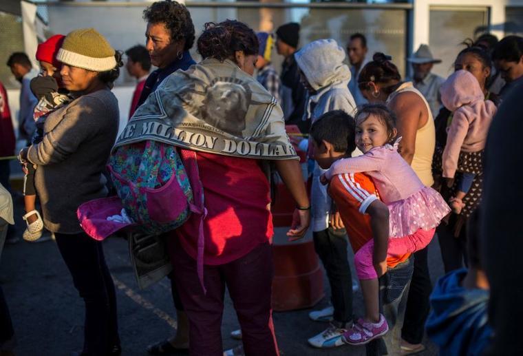 Migrantes se paran en una filas esperando comida donada en Tijuana, México, este domingo 25 de noviembr, mientras intentan llegar a Estados Unidos.