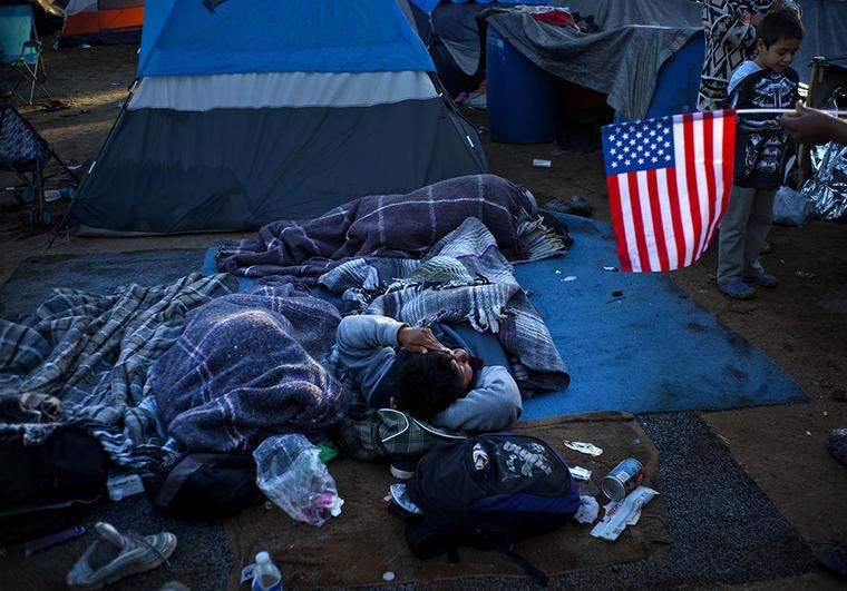 Un inmigrante sostiene la bandera de Estados Unidos mientras descansa en el complejo deportivo Benito Juárez, en Tijuana, México.