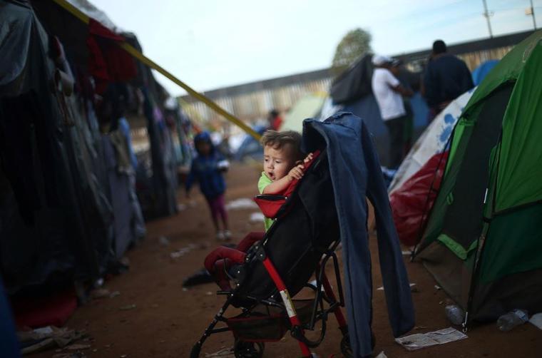 Un bebé migrante, que forma parte de una caravana de miles de personas que viajan desde América Central hacia Estados Unidos, este martes en su cochecito dentro de un refugio temporal en Tijuana, México.