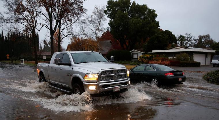 Vehículos atraviesan una calle inundada este jueves 29 de noviembre en Chico, California.