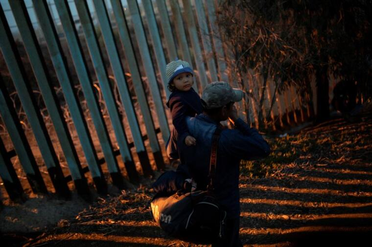 Un migrante de Honduras y una menor este domingo en Tijuana en la frontera con EE.UU. mientras que un grupo de migrantes intenta saltar la valla.