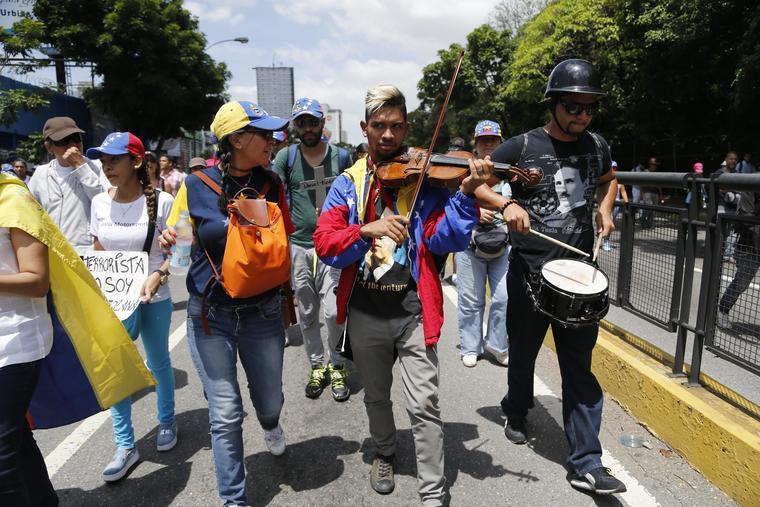 En esta foto del 18 de mayo de 2017, Wuilly Arteaga toca su violín durante una marcha antigubernamental en Caracas, Venezuela. (Foto AP / Ariana Cubillos)