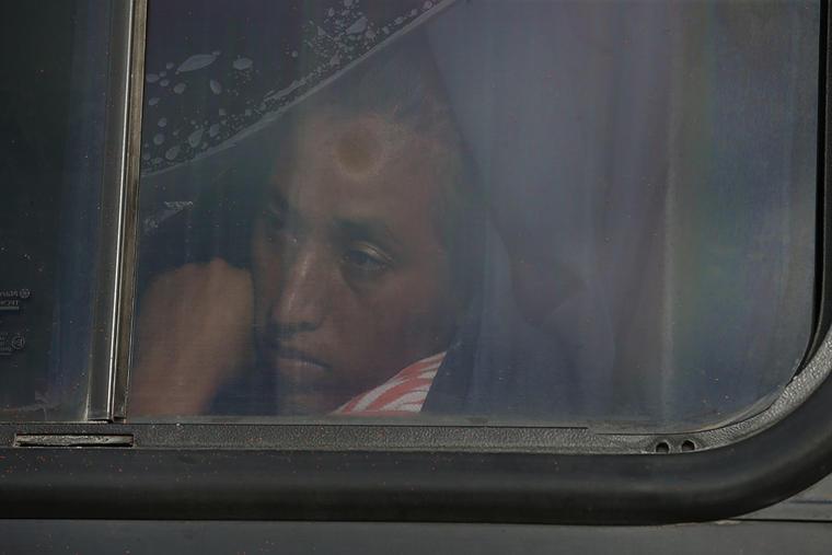 Una mujer mira a través de la ventanilla de un bus que se utilizó para ayudar a los migrantes de la caravana en su camino hacia Estados Unidos.