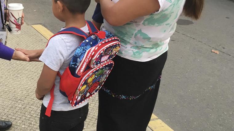 Un estudiante hispano junto a su mamá