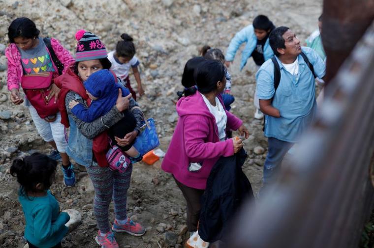 Migrantes centroamericanos junto al muro fronterizo después de cruzar ilegalmente de México a Estados Unidos, visto desde Tijuana, este martes 11 de diciembre de 2018.