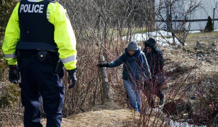 Dos inmigrantes cruzan la frontera hacia Canada en una imagen de archivo.
