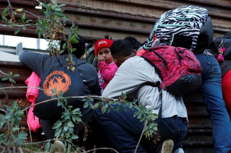 Migrantes hondureños intentan cruzar el muro fronterizo de EE. UU.hacia San Diego, California, desde Tijuana, México, este  sábado 15 de diciembre.