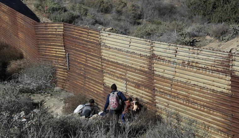 Un grupo de personas intenta cruzar el muro fronterizo en Tijuana (México) el 9 de diciembre.