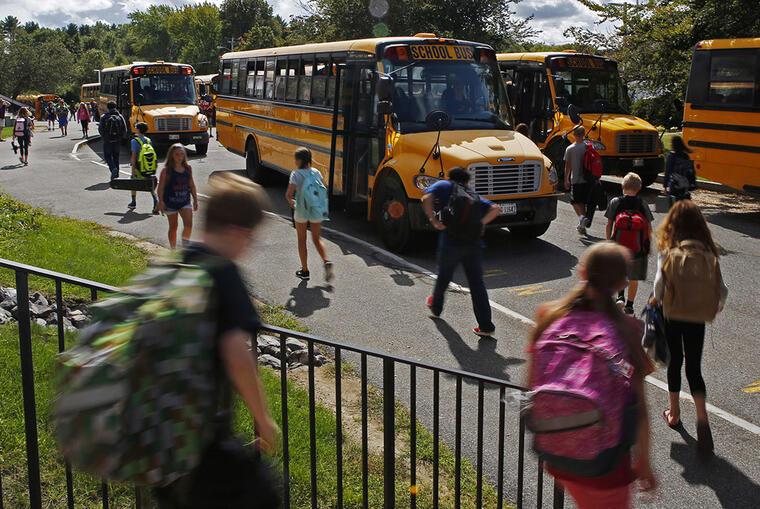 Varios estudiantes se dirigen a los buses escolares tras terminar su día de clases.