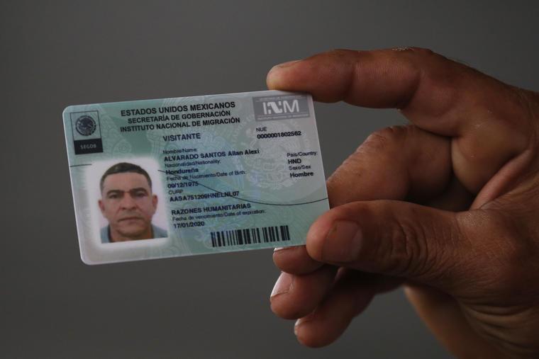 Un emigrante hondureño muestra su visado humanitario en la frontera de México y Guatemala.