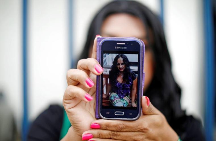 Una amiga de la fallecida Camila Díaz Córdova muestra una foto de la víctima mientras espera en la Oficina del Fiscal General en San Salvador, El Salvador, el 23 de febrero de 2019.