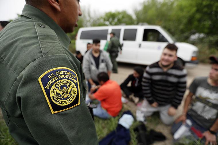Un agente de la Patrulla Fronteriza detienen a varios migrantes que pretendían ingresar ilegalmente a Estados Unidos.