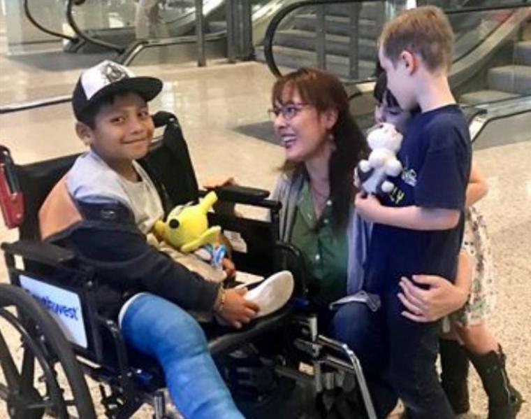 Holly Sewell, de 41 años, y sus dos hijos, Desmond, de 6, y Winifred, de 5, dan la bienvenida a Byron Xol, de 8 años, en el Aeropuerto Internacional de Austin Bergstrom.