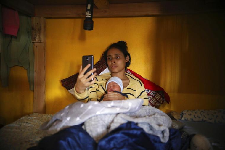 En esta imagen del 12 de junio de 2019, la adolescente migrante Milagro de Jesús Henríquez Ayala, de El Salvador, en la cama con su hijo recién nacido, Alexander, mientras ve Bob Esponja en su celular, en el refugio de la iglesia Ágape Misión Mundial, en