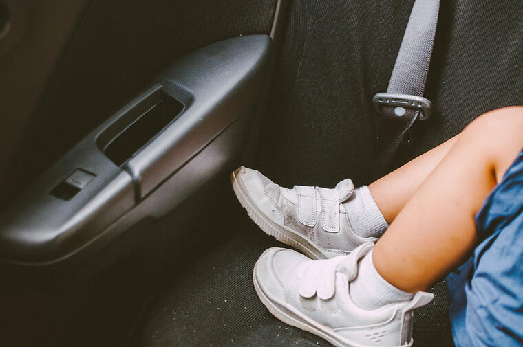 Se muestran los pies de un niño que duerme en la parte trasera de un vehículo.