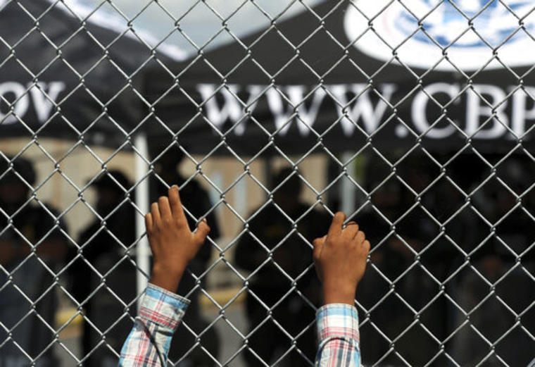 Las manos de una persona migrante apoyadas en una valla en el cruce fronterizo entre Matamoros, México, y Brownsville, Texas.