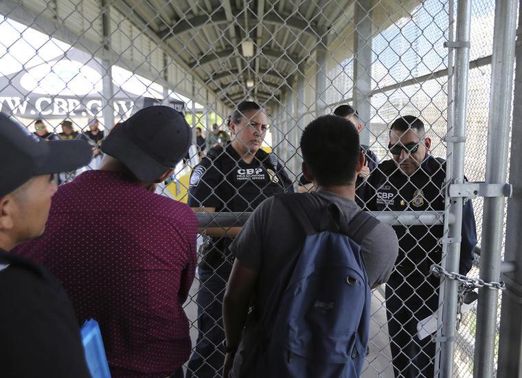 Migrantes lles hacen varias preguntas a oficiales de Aduanas y Protección Fronteriza en el Puente Internacional que conecta a Matamoros, México, con Brownsville, Texas.
