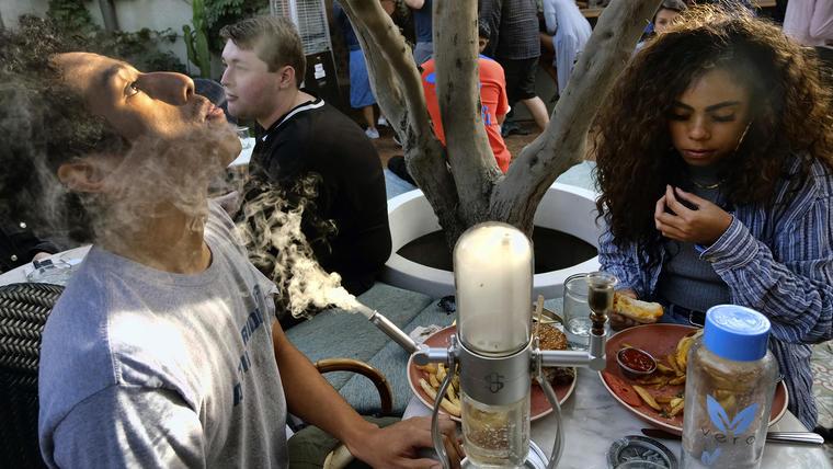 Dos jóvenes fuman marihuana en el Lowell's Original Cannabis Cafe, en Los Ángeles.