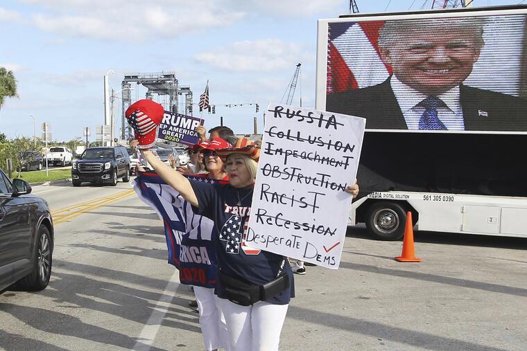 Un grupo de personas espera con carteles de apoyo el paso del vehículo de Trump en su residencia de Mar-a-Lago (Florida) este domingo.