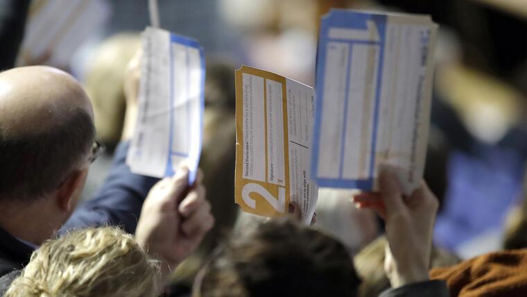 Participantes de los caucus levantan sus votos en el campus de la Drake University, en Des Moines, Iowa.