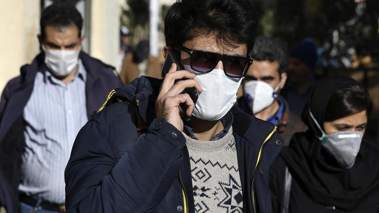 Un hombre usando una mascarilla habla por celular, en Irán.