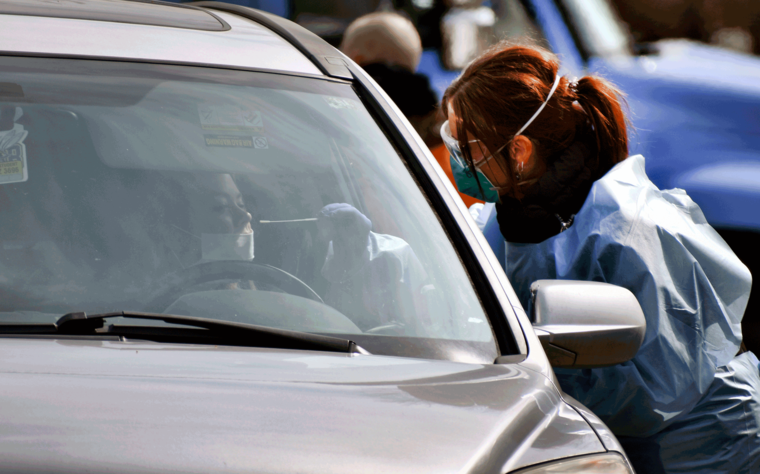 Una enfermera toma muestras de una paciente para una prueba de coronavirus.
