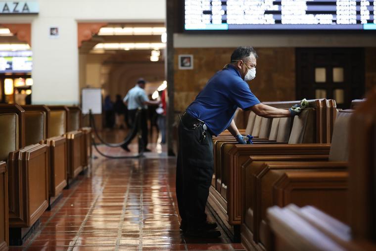 Los asientos en un área de espera son limpiados por un miembro del personal de limpieza debido al coronavirus, en Union Station el 13 de marzo de 2020 en Los Ángeles, California.