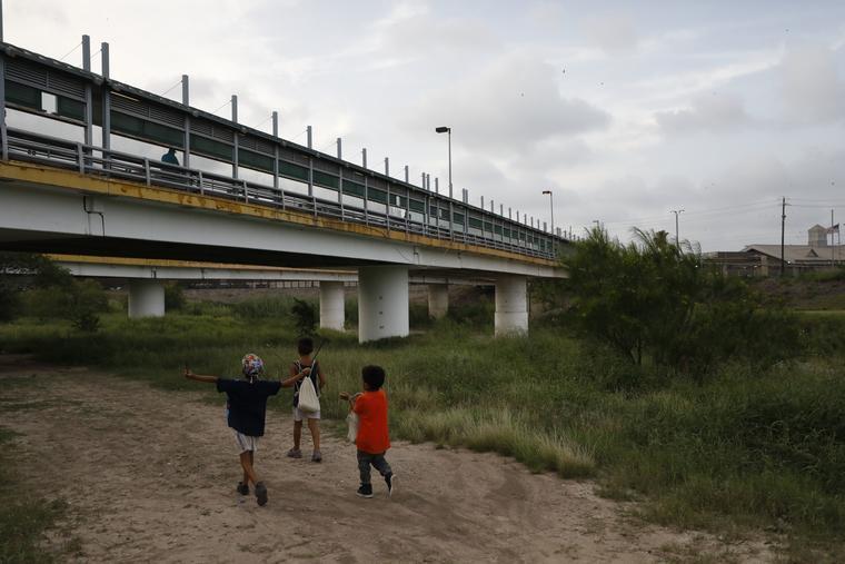 Niños migrantes caminan con sus familias a lo largo de Río Grande