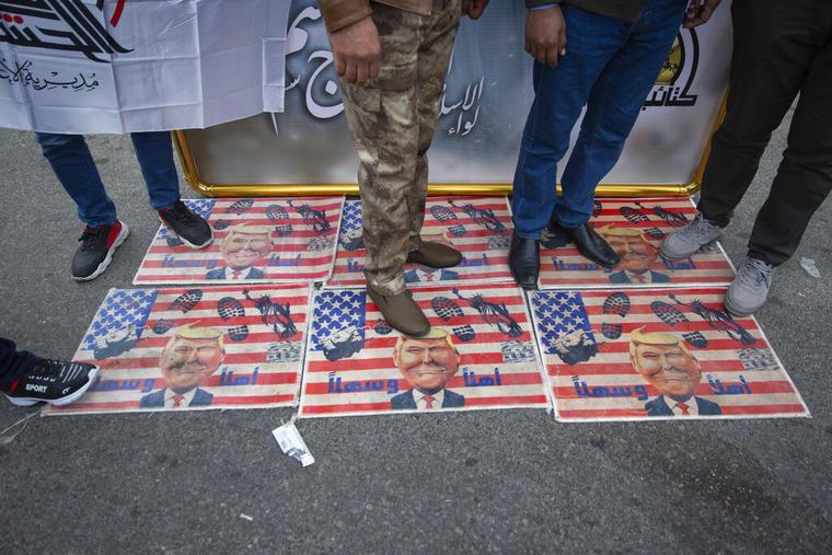 Participantes en el funeral del general Soleimani en Irak pisan banderas estadounidenses con imágenes del presidente Trump.