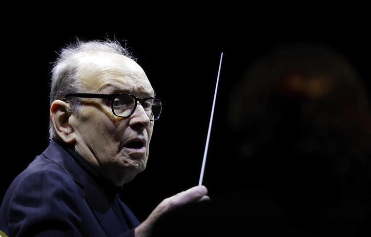 El compositor italiano Ennio Morricone dirige una orquesta durante un concierto de 2018 en Milán, Italia.